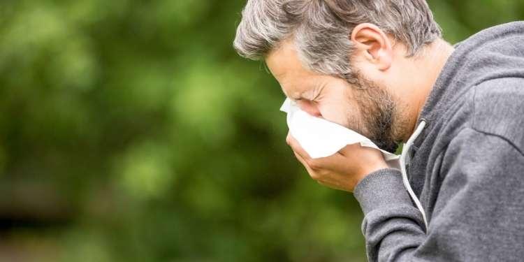 A man sneezes into a handkerchief because he has seasonal allergies.