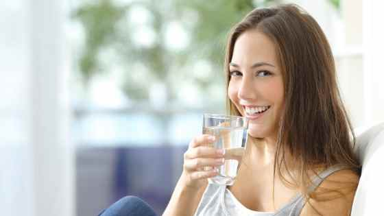 woman drinking water and smiling
